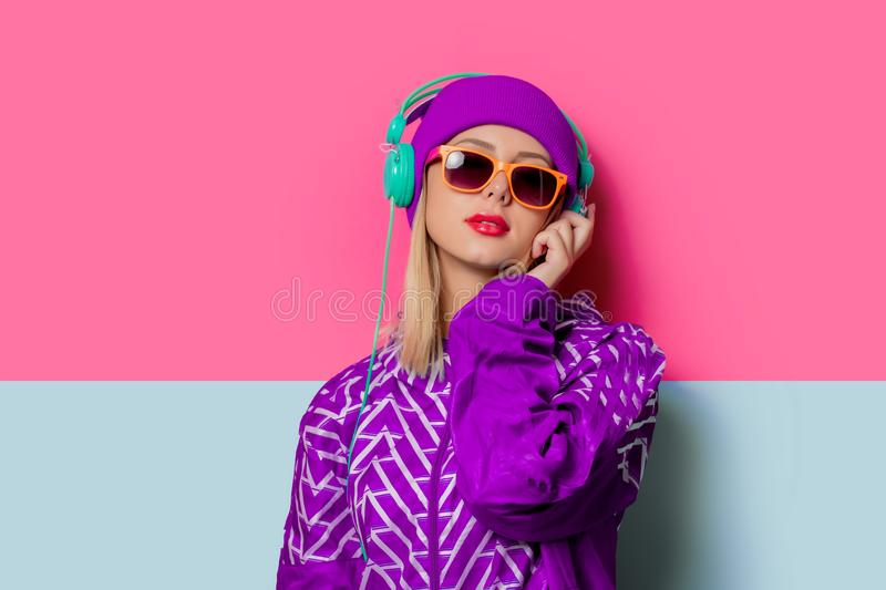 Young blonde girl in 90s sports jacket and hat. On pink and blue background royalty free stock photo
