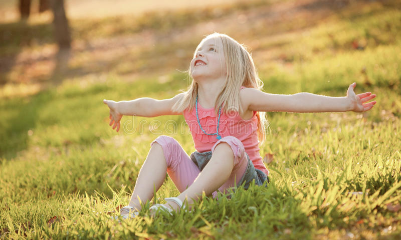 A young blonde girl sitting on the grass in the back light in summer. She has her arms out representing freedom, surrender or ha stock photography