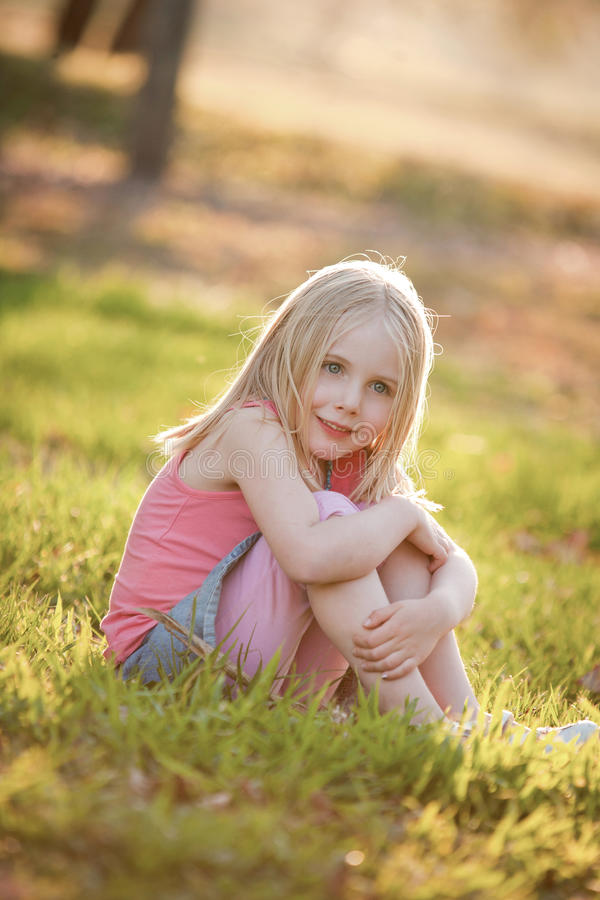 A young blonde girl sitting on the grass in the back light in summer. She is sitting down smiling and looking at the camera. royalty free stock photo