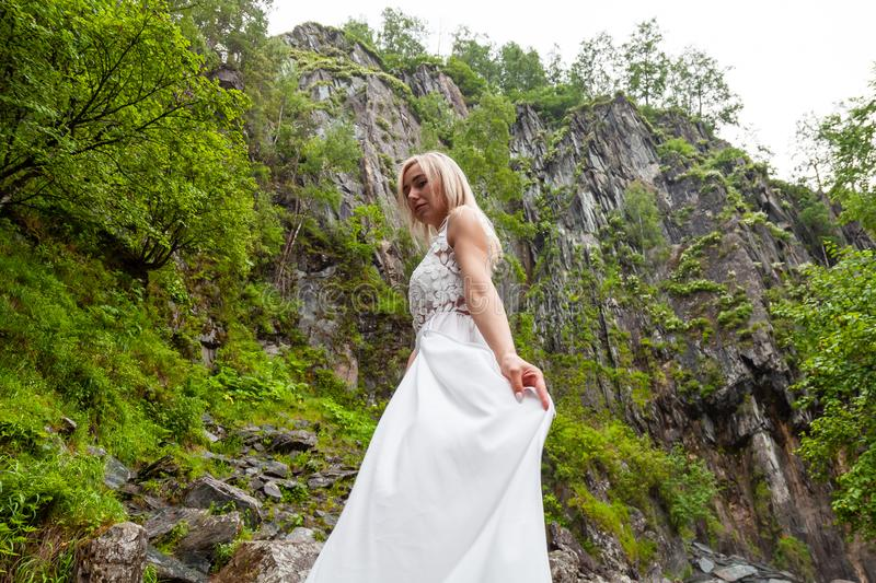 A young blonde girl standing in a half-turn hand straightens a boudoir dress in the mountains against a waterfall and stones like. A ballerina on a warm summer royalty free stock photography