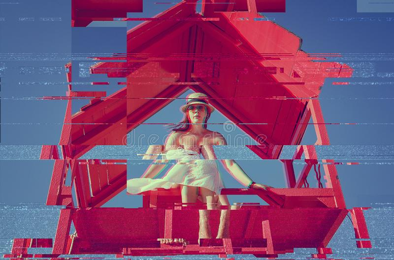 A young blonde girl in a straw hat and white dress sits on a red rescue tower on the beach of Egypt against a blue sky. Glitch stock image