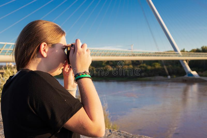 Young blonde girl taking pictures on a bridge royalty free stock photography