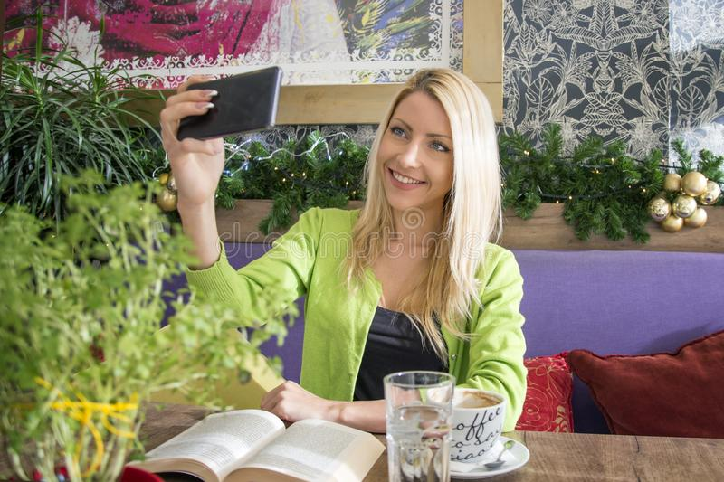 Blonde girl taking selfie in cafe. Young blonde girl taking selfie by mobile phone and smile on cafe stock image