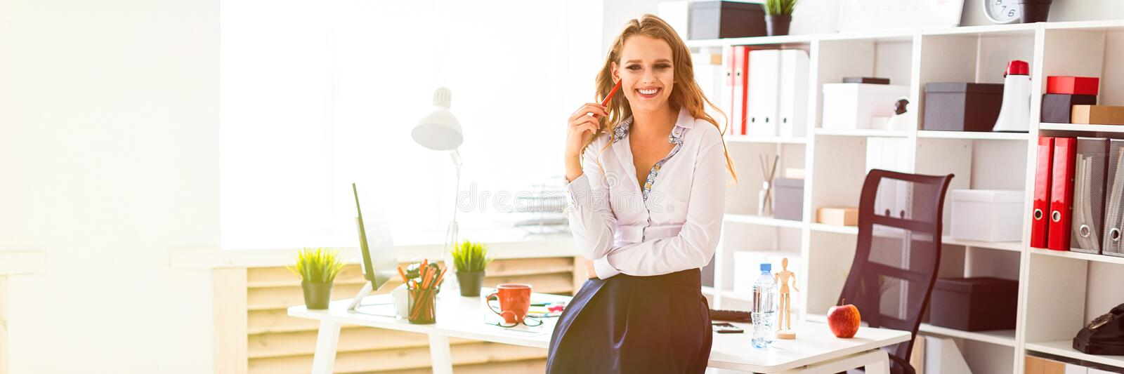 A beautiful young girl stands near a table in the office and holds a red pencil in her hands. royalty free stock images