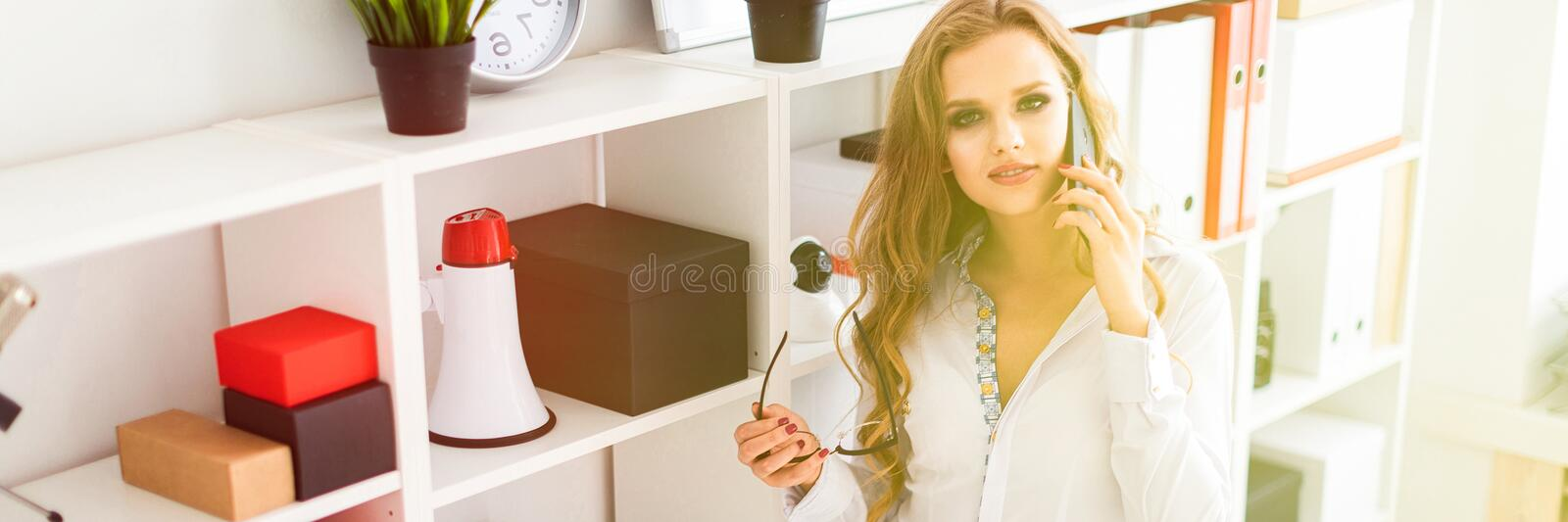 A beautiful young girl stands near a rack in the office, talking on the phone and holding glasses in her hand. royalty free stock photography