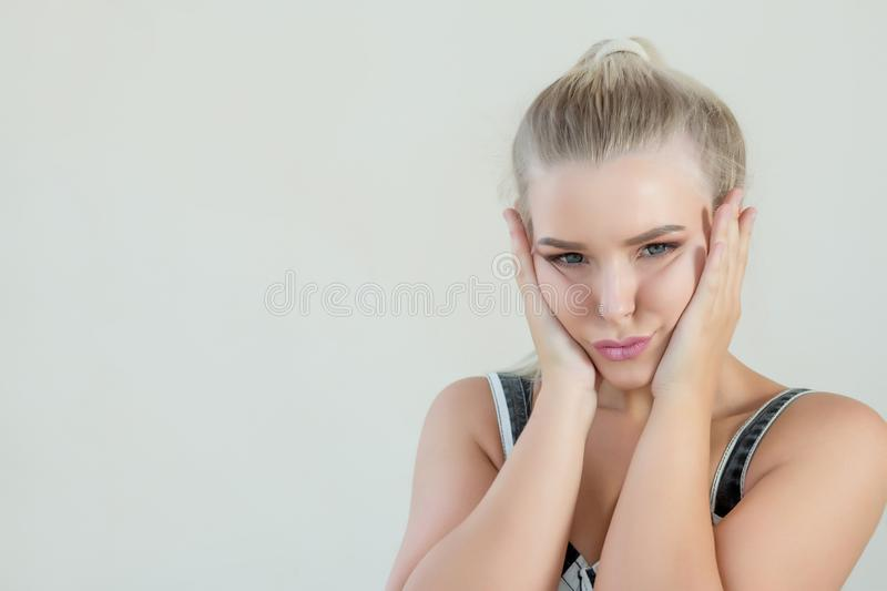 Young blonde grimacing woman holding her cheeks. Space for text stock image