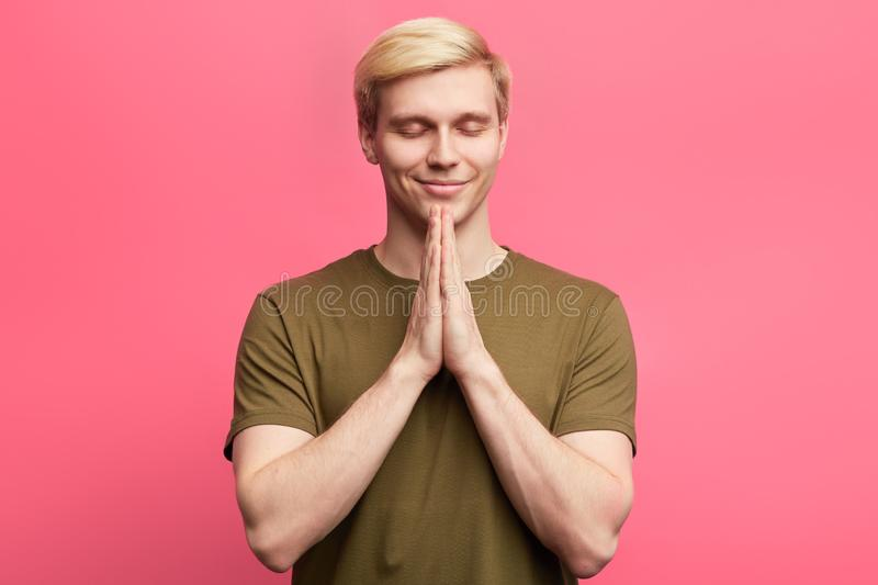 Young blonde guy puts hands together in prayer or meditation royalty free stock photography