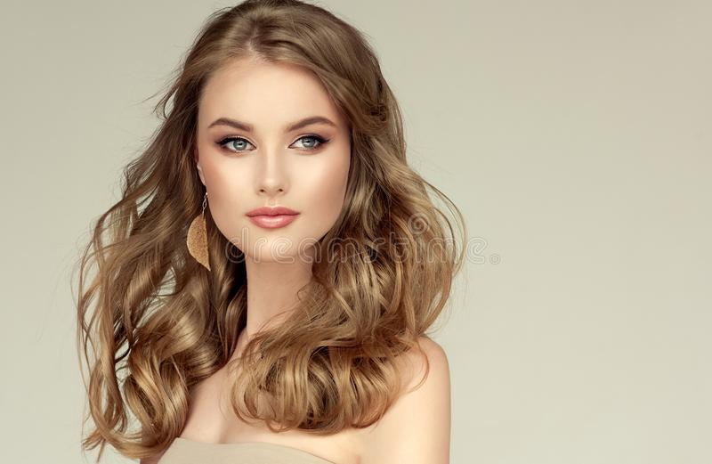 Young, blonde haired beautiful model with long, well groomed hair, dressed in golden earrings. Perfect freely laying hairstyle. royalty free stock images