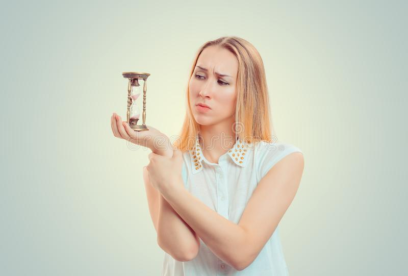 Upset gloomy woman looking at hourglass stock images