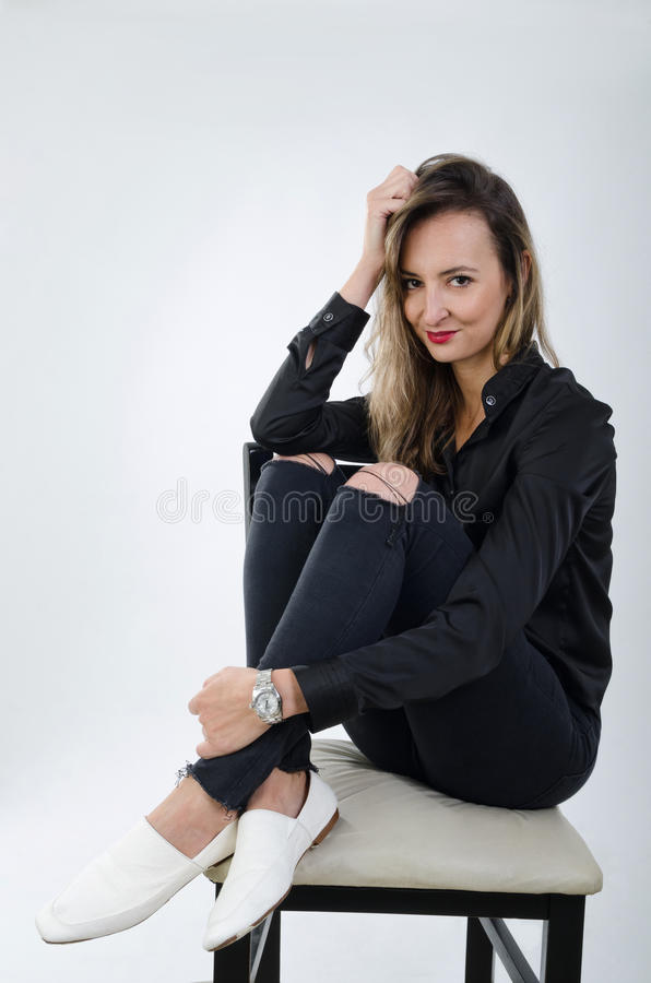 Young blonde lady smiling sitting on a chair. Young lady crosslegged wearing a black t-shirt, blue jeans and white shoes royalty free stock photos