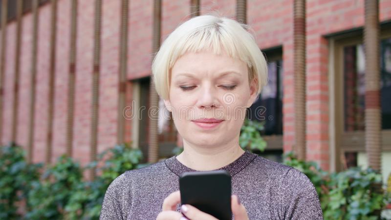 Young Blonde Lady Using a Phone in Town stock images