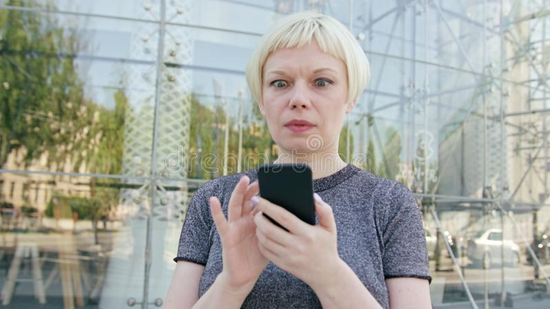 Young Blonde Lady Using a Phone in Town stock image