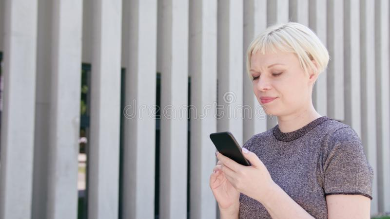 Young Blonde Lady Using a Phone in Town stock photos