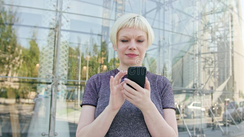 Young Blonde Lady Using a Phone in Town royalty free stock photo