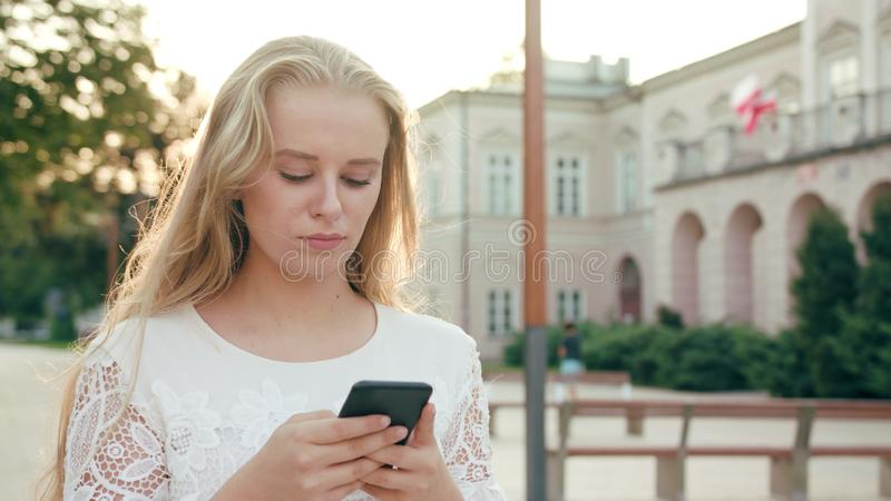 Young Blonde Lady Walking and Using a Phone in Town royalty free stock photo