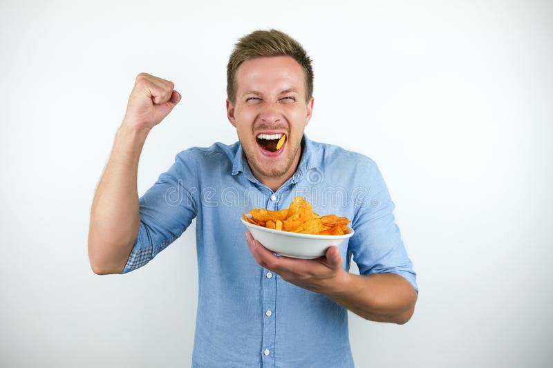 Young blonde man eats chips holding his fist up happily on isolated white background stock photography