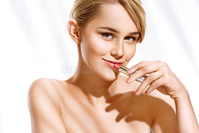 Young blonde model applying lipstick. royalty free stock image