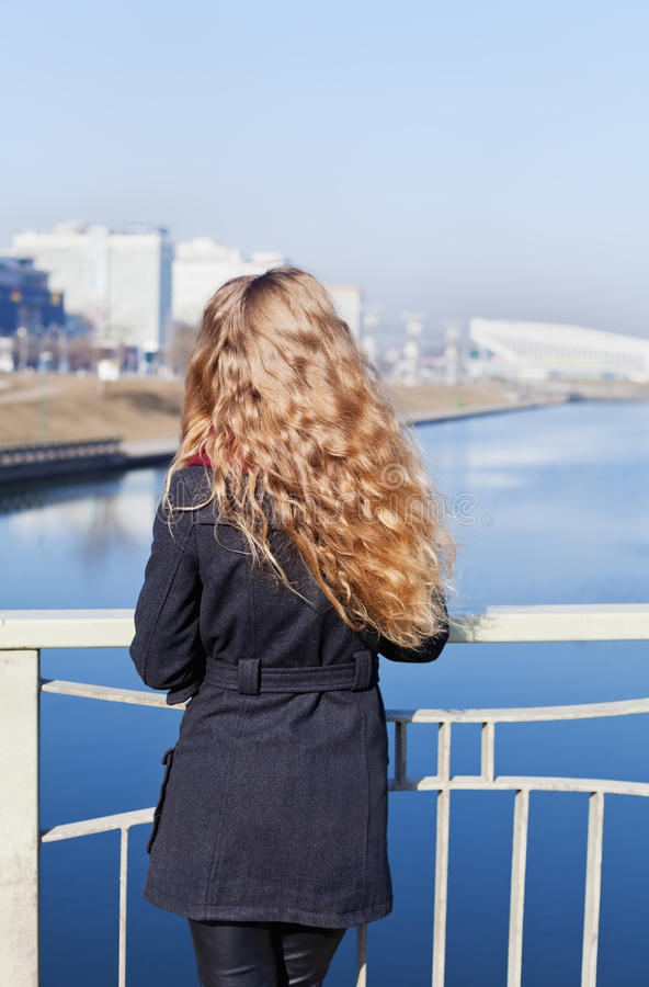 Young blonde model girl with long curly hair standing on the bridge and looking at the river and city in windy day royalty free stock photography