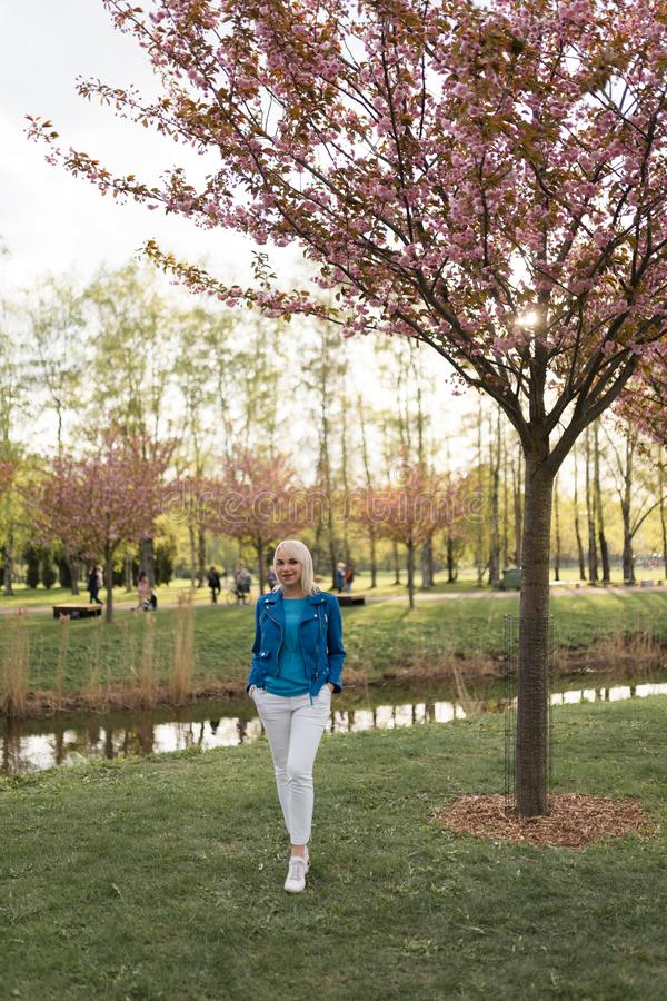 Young blonde mother woman enjoying free time - Dressed in blue jacket and white pants stock photo