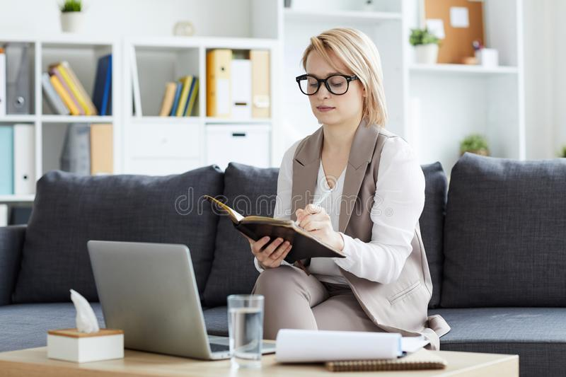 Planning work in office. Young blonde serious counselor making working notes in notepad while organizing work in her office stock photos