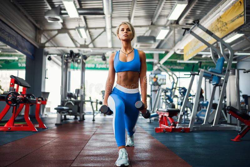 Young blonde girl doing squat. Young blonde girl in the gym doing squat with dumbbells royalty free stock photo