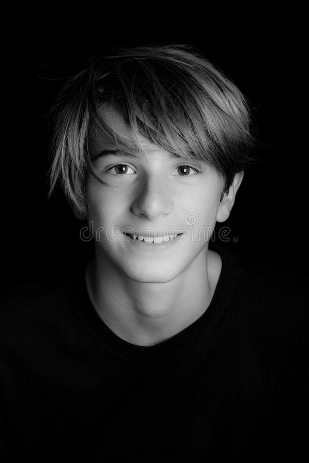 Young blonde smiling guy portrait on black background - black an stock images