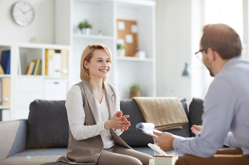 Solving problems. Young blonde smiling women sitting on couch and looking at counselor during discussion of ways of solving problem royalty free stock photography