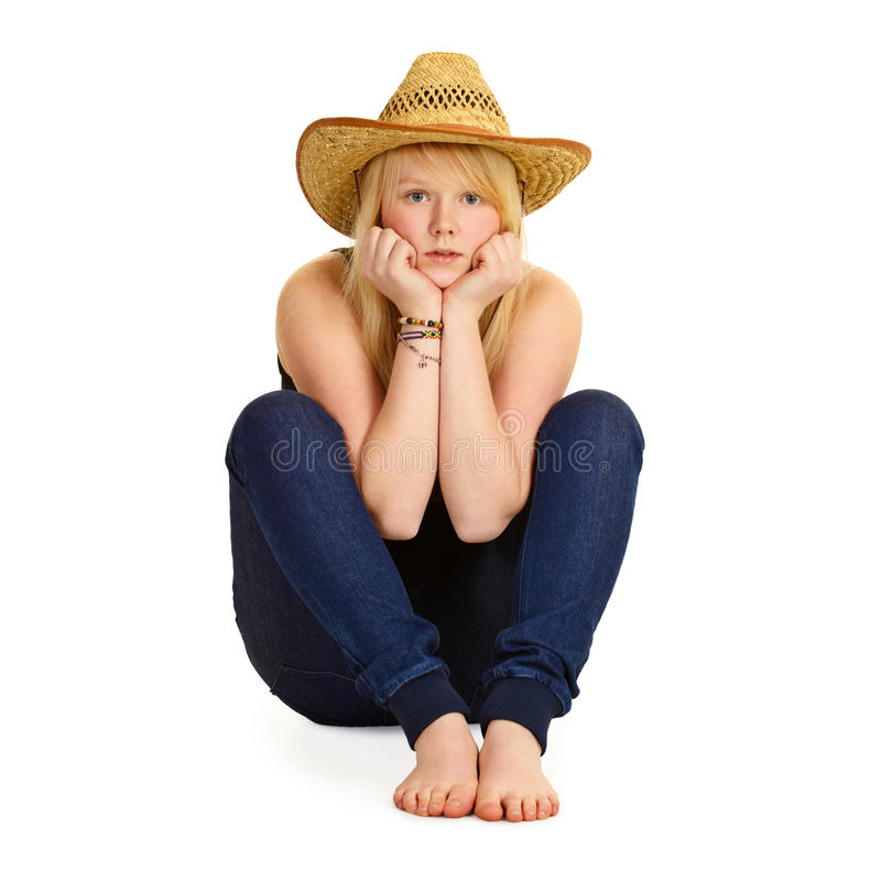 Young blonde in straw hat sitting on floor royalty free stock images
