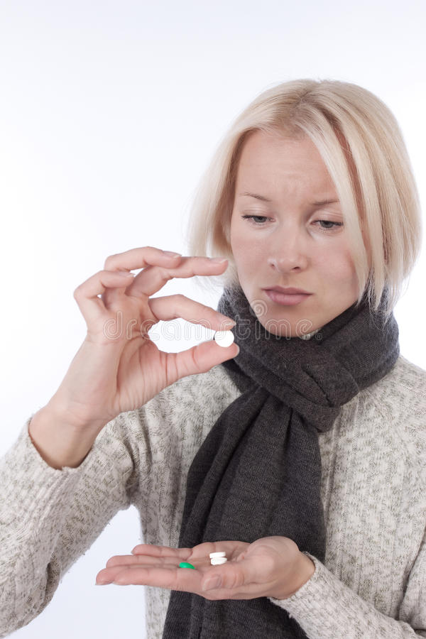 Young blonde taking tablets stock photos