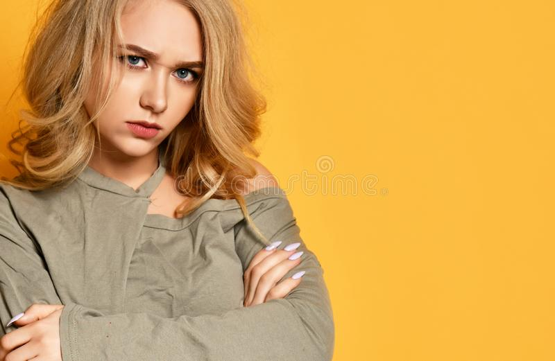 Young blonde upset girl in short blouse with crossed arms is offended much, looks angry and blame somedody. royalty free stock photography