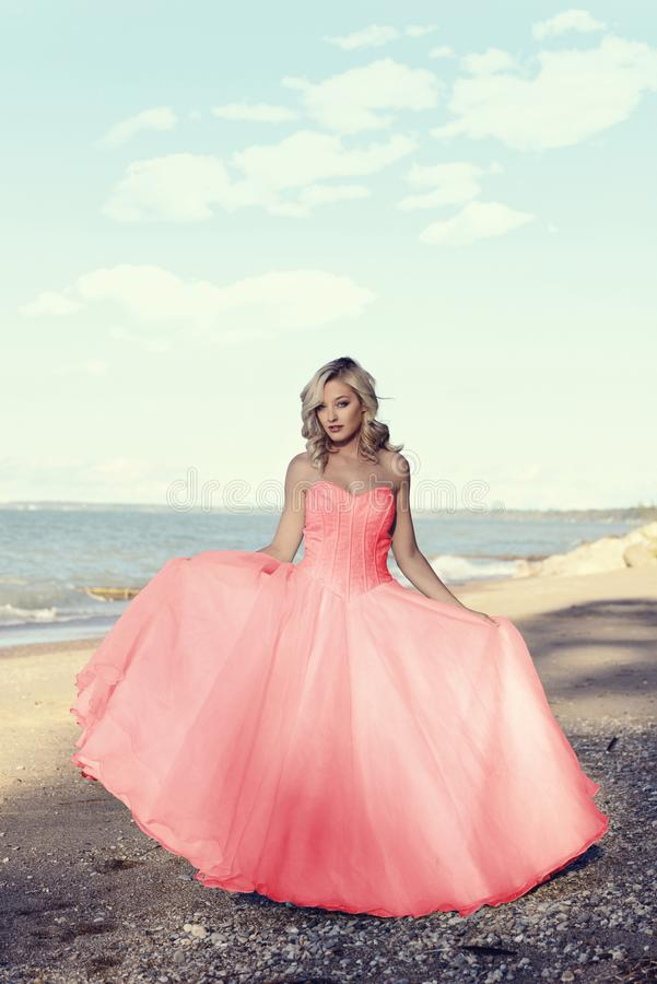 Free Young Blonde Woman At The Beach With Red Tulle Ball Dress Stock Photography - 101937582
