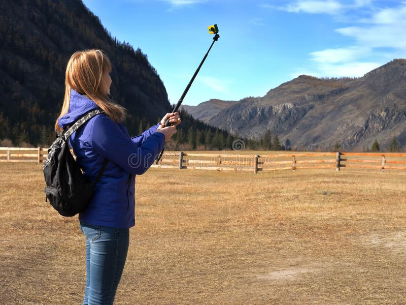 Young blonde woman backpacker taking photo with action camera on mountain peak. stock images