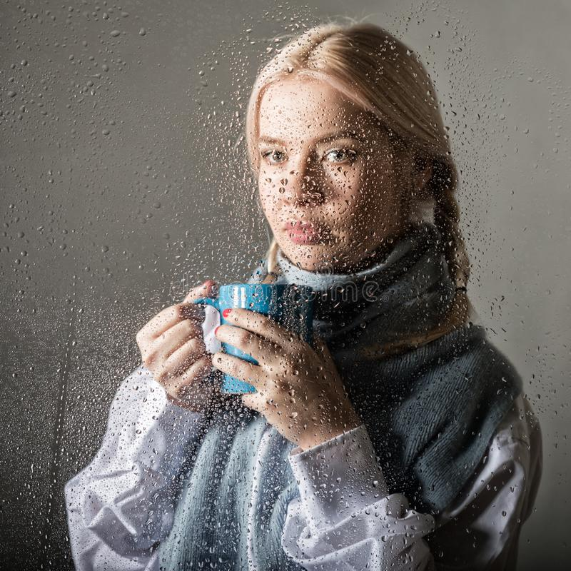 Young blonde woman behind glass with water drops. beautiful girl drinks coffee or tea royalty free stock photography