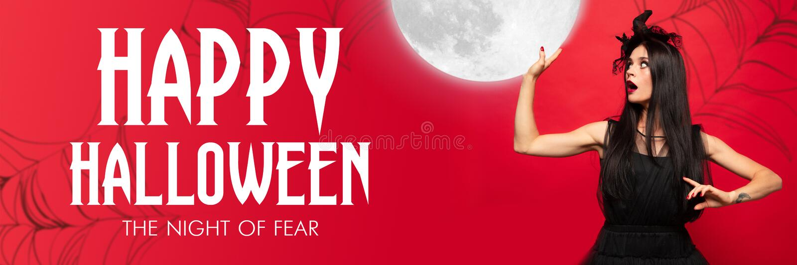 Young woman in hat as a witch on scary red background. Young blonde woman in black hat and costume on red background. Attractive caucasian female model holding stock images