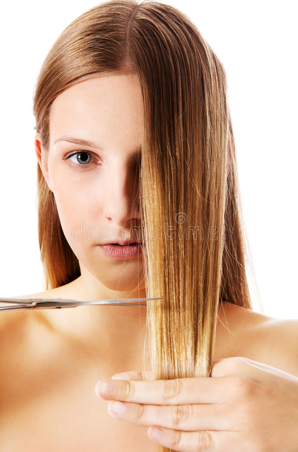 Young blonde woman cutting her hair with scissors. stock image