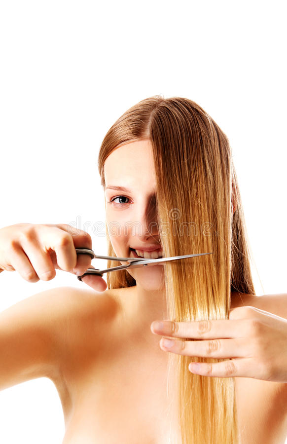 Young blonde woman cutting her hair with scissors. royalty free stock photo
