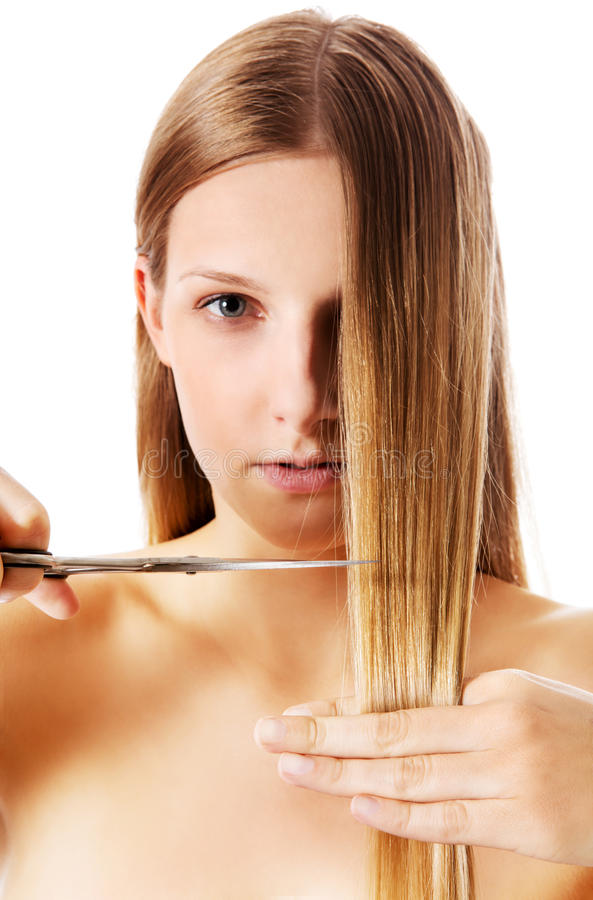 Young blonde woman cutting her hair with scissors. royalty free stock image