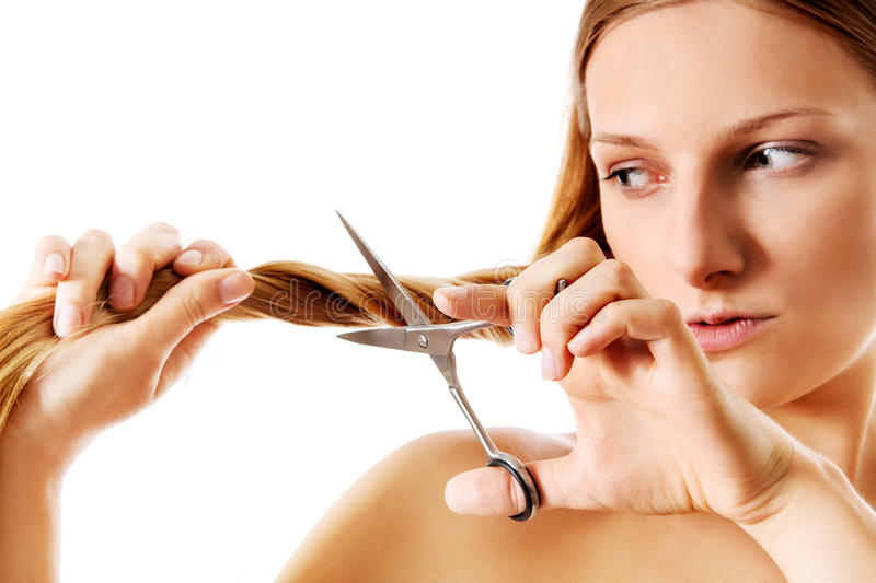 Young blonde woman cutting her hair with scissors. stock images