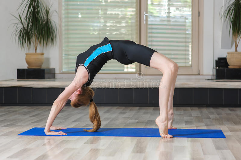 Young blonde woman doing gymnastics exercises. royalty free stock photo