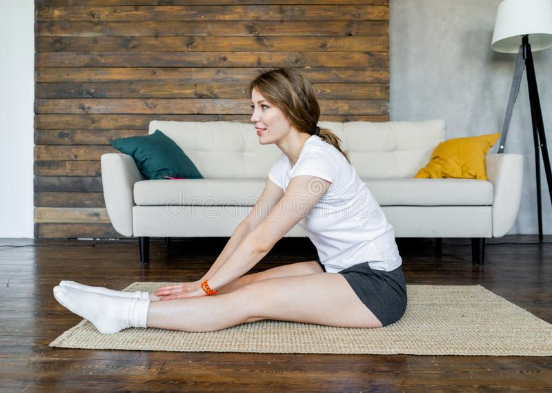 Young blonde woman doing stretching yoga exercises at home. Healthy lifestyle stock photos