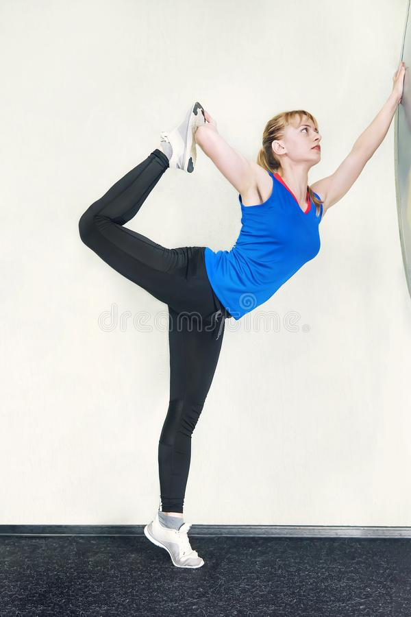 Young blonde woman doing a yoga pose standing on one leg and stretching near a white wall. Utthita Hasta Padangusthasana royalty free stock photo