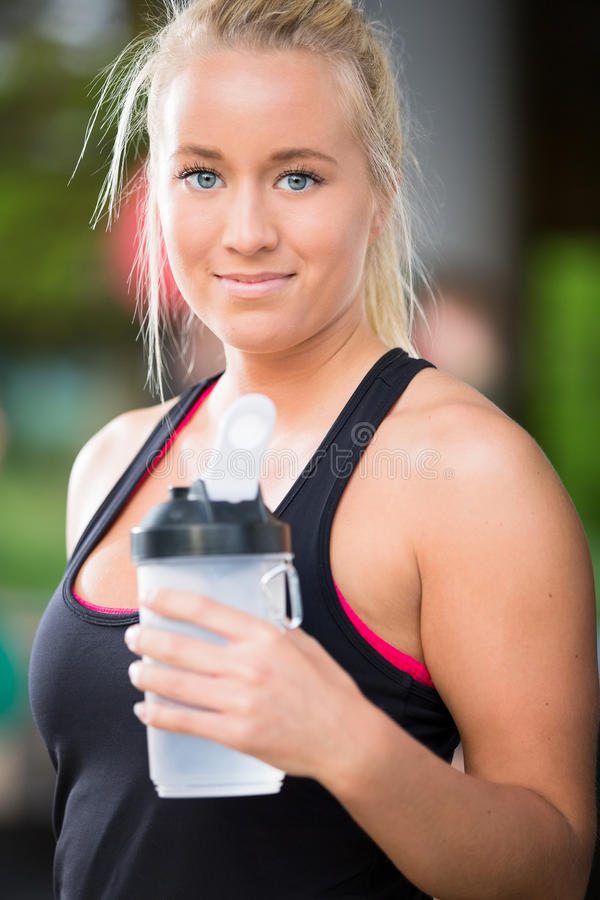 Young blonde woman drink water at crossfit center royalty free stock photos