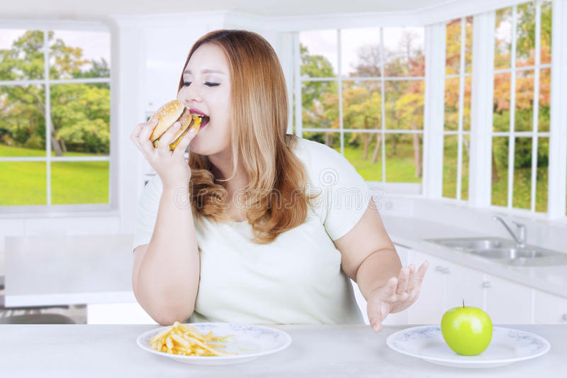 Young blonde woman eats burger. Picture of a young blonde woman choosing to eat hamburger and refusing apple fruit in the kitchen at home stock photography