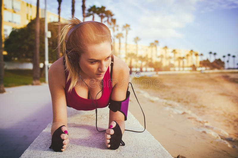 Young blonde woman exercising on beach royalty free stock images