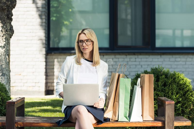 young blonde woman in eyeglasses using laptop while sitting on bench stock photo