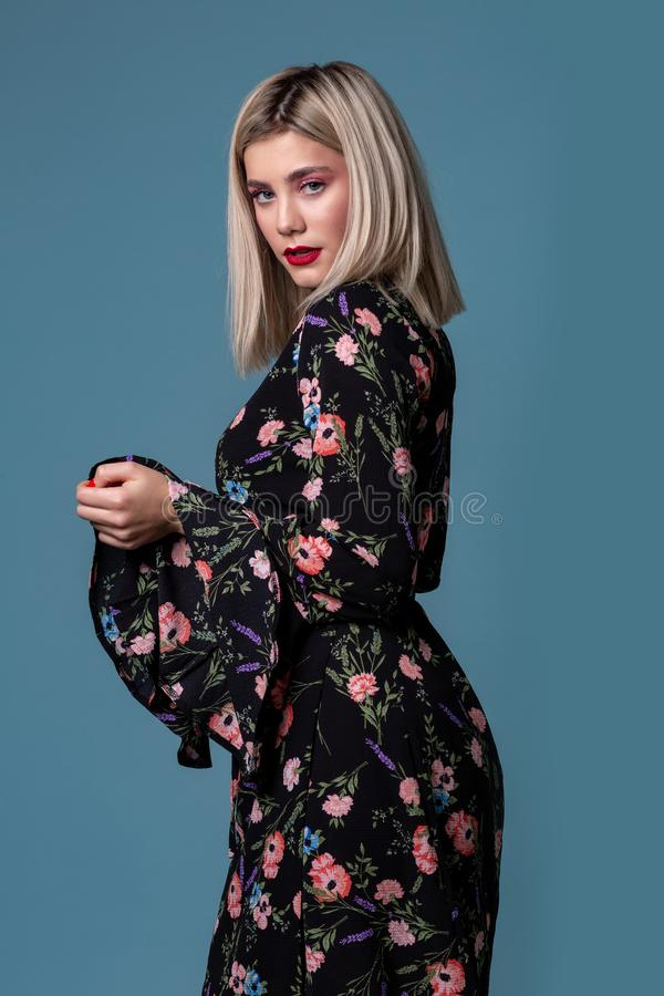 Young blonde woman in floral summer dress on a blue background royalty free stock images