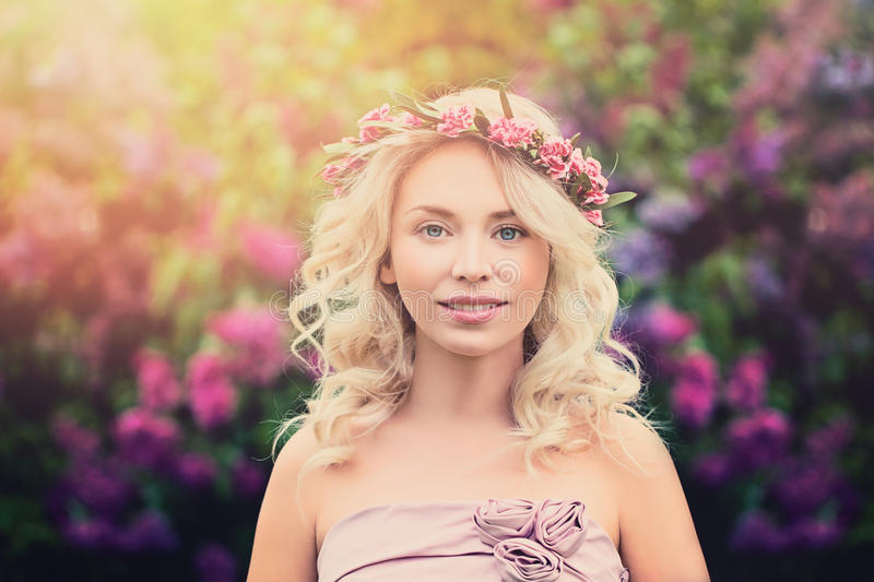 Young Blonde Woman with Flower Wreath and Sunlight stock photo