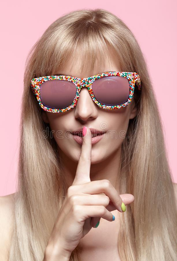 Young blonde woman with fun candy glasses and finger on lips on stock photos