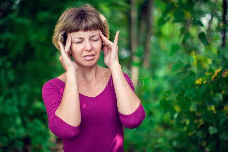 Young blonde woman having serious migrene suffering from horrible head ache feeling big pain outdoor. Healthcare, medicine and pe royalty free stock image