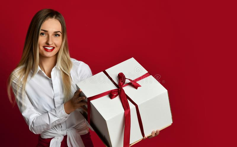 Young blonde woman hold white box gift present smiling try to open it on Birthday party celebration on red royalty free stock photo